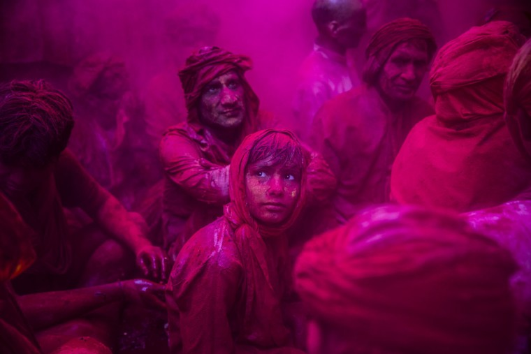 A boy looks on as Hindu devotees play with color during Lathmar Holi celebrations on March 21, 2013 in the village of Barsana, near Mathura, India. (Daniel Berehulak/Getty Images)