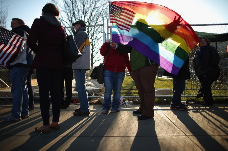 Heather Davidson and Julie Berger (C), both of Shelbyville, Indiana, hold up a pride flag while standing in line with hundreds of others outside the Supreme Court for a chance to hear oral arguments March 27, 2013 in Washington, DC. (Chip Somodevilla/Getty Images)