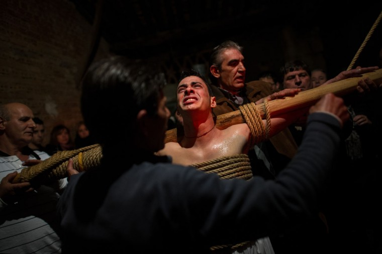 March 29, 2013: Relatives undress Cesar Higuero Martin, aged 25, after walking the way of the cross or 'Via Crucis' at the end of the procession of the 'Empalaos' in Valverde de la Vera, Spain. Empalaos make the steps of the 'Via Crucis', marking the Stations of the Cross, during the night of Maundy Thursday while bound by rope to a crucifix as an act of penance and to honour a promise made to the Empalaos Brotherhood and the Christ of Vera Cruz, in the town of Valverde de la Vera. (David Ramos/Getty Images)