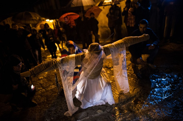 March 29, 2013: Cesar Higuero Martin, aged 25, prays at one station of the way of the cross or 'Via Crucis' during the procession of the 'Empalaos' in Valverde de la Vera, Spain. The process of dressing the Empalao in the traditional costume is taken with great care, with the family and dressers paying attention to ensure that no harm is caused to the penitent and that they are aided in their recovery, including being massaged and rubbed with rosemary alcohol. (David Ramos/Getty Images)