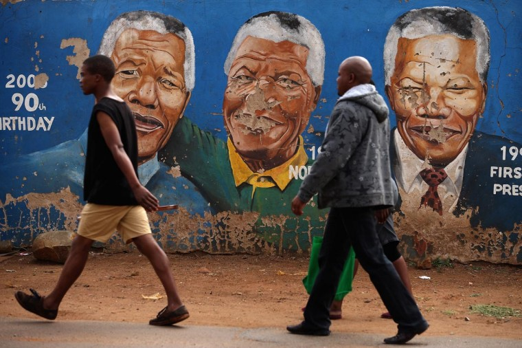 "A family walks past a mural depicting former South African President Nelson Mandela during different times in his life near the Regina Mundi Catholic Church in the Soweto area March 31, 2013 in Johannesburg, South Africa. A central gathering place during he anti-apartheid struggle, the church held prayers for Mandela, 94, who is in the hospital for the third time since December with lung problems. Referring to Mandela by clan name, Madiba, President Jacob Zuma said, ""We appeal to the people of South Africa and the world to pray for our beloved Madiba and his family and to keep them in their thoughts."" Mandela's lungs were damaged when he contracted tuberculosis during his 27 years in the infamous Robben Island prison. Mandela became the nation's first democratically elected president in 1994 following the end of apartheid. (Chip Somodevilla/Getty Images)"