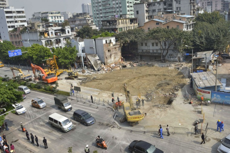 This picture taken on January 29, 2013 shows rescuers filling the sinkhole that buildings collapsed into the night before near a subway construction site in Guangzhou, south China's Guangdong province. The hole measured about 1,000 square feet across and was around 30 feet deep, but no one was killed, according to a state media report. (STR/AFP/Getty Images)