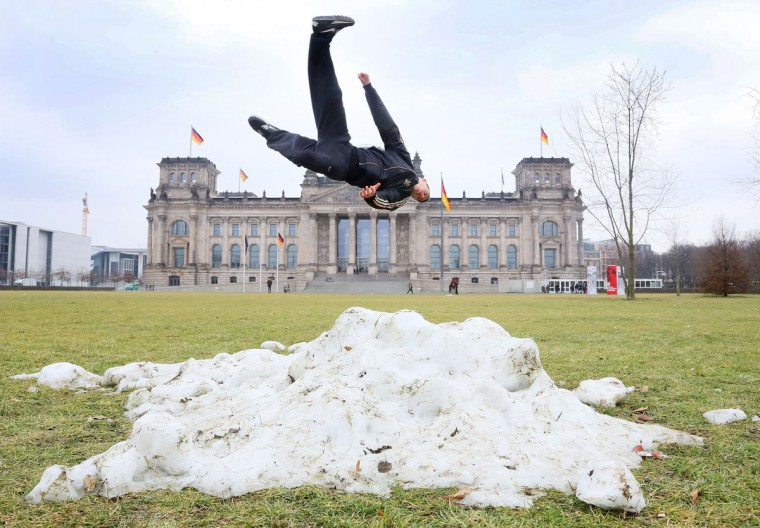 Hadi from Denmark jumps over one of the last heaps of snow during a stop of his tourist group in front of the Reichstag Building in Berlin, on February 28, 2013. (Stephanie Pilick/AFP/Getty Images)