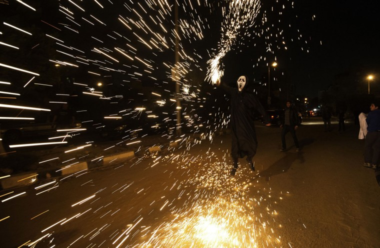 """An Egyptian activist ignites fireworks following a performance by Egyptian activists and youth of the internet craze """"Harlem Shake"""" in front of the Muslim Brotherhood headquarters in Cairo on February 28, 2013. (Gianluigi Guercia/AFP/Getty Images)"""