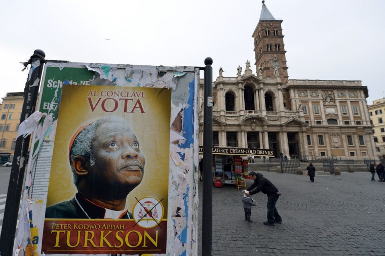 """A fake electoral placard showing Ghana's Cardinal Peter Turkson, seen by some as Africa's top candidate to become the next pope and reading """"during the conclave, vote Turkson"""" is displayed in front of the Santa Maria Maggiore basilica in Rome. Catholic cardinals from around the world were summoned Friday to meetings that will set a date for a conclave to elect a new pope, the day after Benedict XVI's historic resignation. (Alberto Pizzoli/AFP/Getty Images)"""