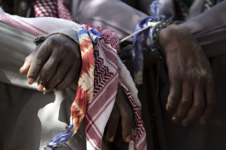 Prisoners' hands are bound together as they arrive by boat escorted by Malian soldiers in Kadji, on the Niger river. French and Malian troops launched an operation yesterday in the village of Kadji, northern Mali, where Islamists are hiding out on an island in the Niger river, a military source told AFP. (Joel Saget/AFP/Getty Images)