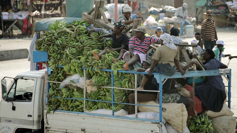 Haitians travel in a truck loaded with bananas in a shantytown in Port-au-Prince on March 2, 2013. Brazil began the process of reducing its peace-keeping forces operating under the MINUSTAH mandate from 1910 to 1450 men, the same number that was there before the deadly 2010 earthquake that left a death toll of more than 250,000. (Vanderlei Almeida/AFP/Getty Images)