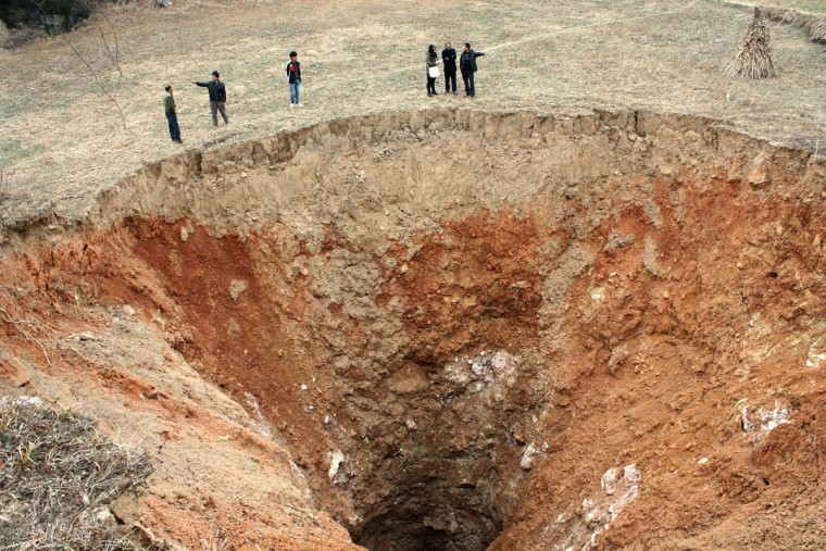This picture taken on February 25, 2013 shows people standing beside an enormous hole in the ground in Guangyuan, a village in southwest China's Sichuan province. Now the hole currently measures 24.9 metres in diameter and local residents fear the pit will continue to grow until it starts swallowing nearby houses. (AFP/Getty Images)