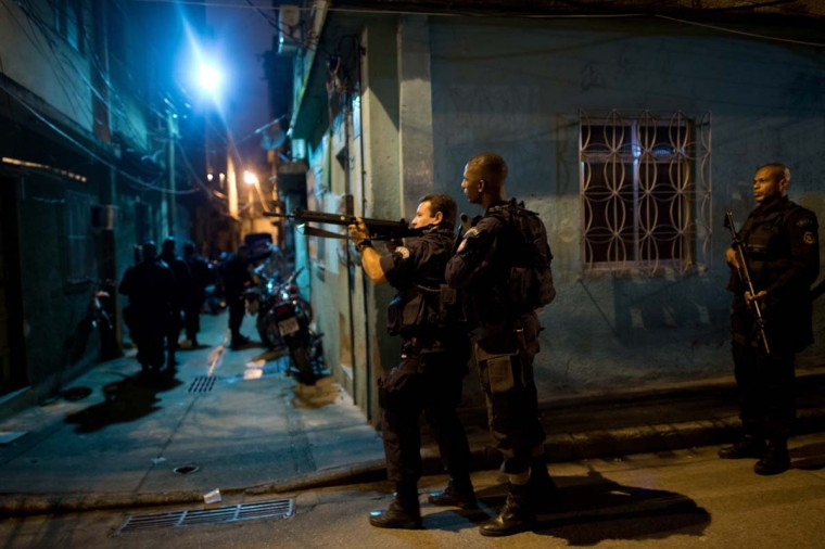 Brazilian BOPE police elite unit personnel patrol during an operation at Caju shantytown in Rio de Janeiro, Brazil, early morning March 3, 2013. Brazilian police on Sunday occupied crime-infested slums near Rio de Janeiro's international airport and seaport as part of efforts to drive out drug traffickers ahead of the 2014 World Cup. The operation, which began at 4:55 am local time, involved more than 1,300 police and members of the military backed by mechanized units of the Brazilian navy, which entered the favelas of Caju and Barreira do Vasco and seized control of their narrow streets. (Christophe Simon/AFP/Getty Images)