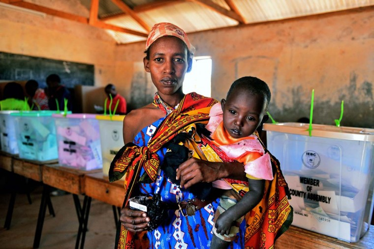 A Maasai woman is pictured with her child after casting her vote in Ilngarooj, Kajiado County, Maasailand, on March 4, 2013 during the nationwide elections. Long lines of Kenyans queued from way before dawn to vote Monday in the first election since the violence-wracked polls five years ago, with a deadly police ambush hours before polling started marring the key ballot. (Carl de Souza/AFP/Getty Images)