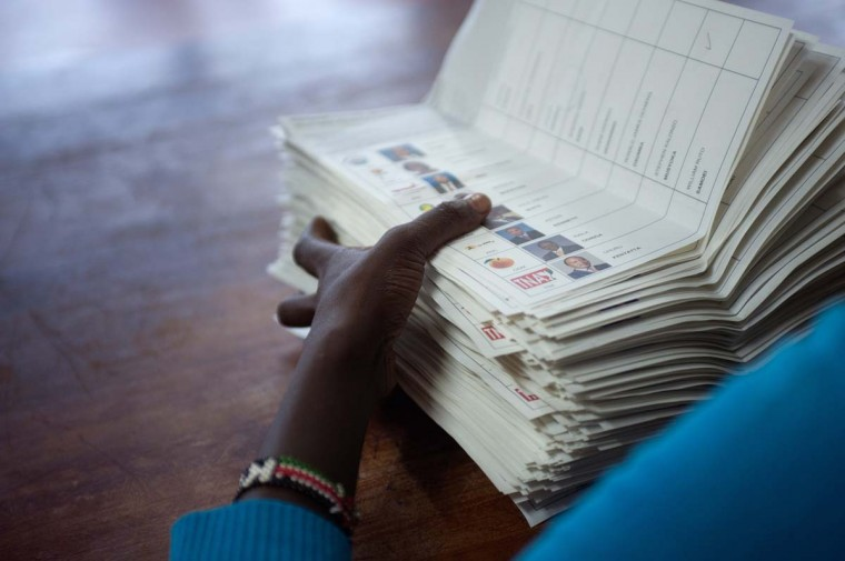 A voting assistant stacks ballot papers marked with a vote for presidential candidate Raila Odinga to an assistant at the Olympic Primary School in Kibera, Nairobi on March 4, 2013. (Will Boase/AFP/Getty Images)