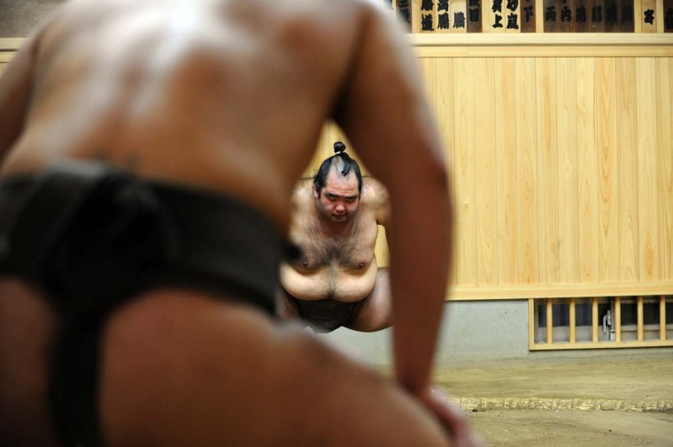 This photo taken on February 14, 2013 shows sumo wrestler Moriurara (background C) exercising with other wrestlers during a training session at a sumo stable in Tokyo. Most of the 610 wrestlers who come under the aegis of the venerable Japan Sumo Association are lodged in stables like this one; living, eating and sleeping together in facilities that allow for little personal space. (Toshifumi Kitamura/AFP/Getty Images)