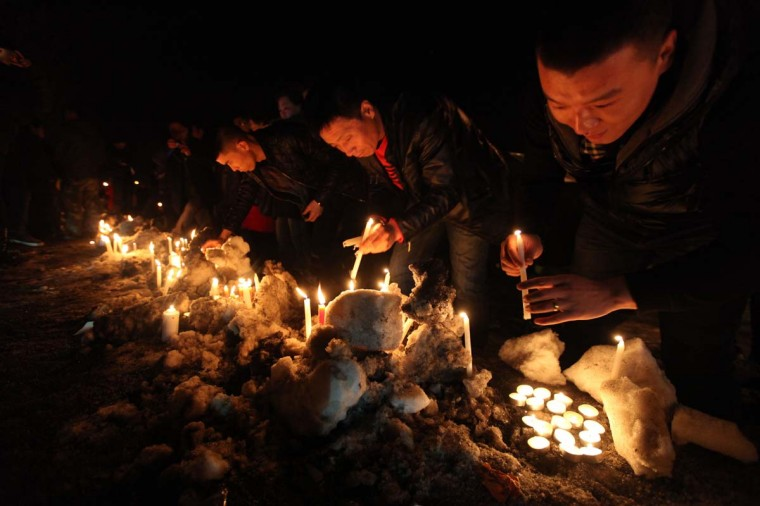This picture taken on March 5, 2013 shows Changchun citizens gathered together to mourn the death of a two-month-old baby killed by a car thief in Changchun, northeast China's Jilin province. The thief strangled the baby to death after stealing a vehicle with the infant inside, police said, provoking outrage across the country on March 5, 2013. (AFP/Getty Images)