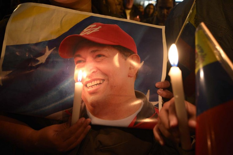 A supporter of Venezuelan President Hugo Chavez holds a poster of him and a candle outside the Venezuelan embassy in Quito on March 5, 2013, after knowing of his death. (Rodrigo Buendia/AFP/Getty Images)