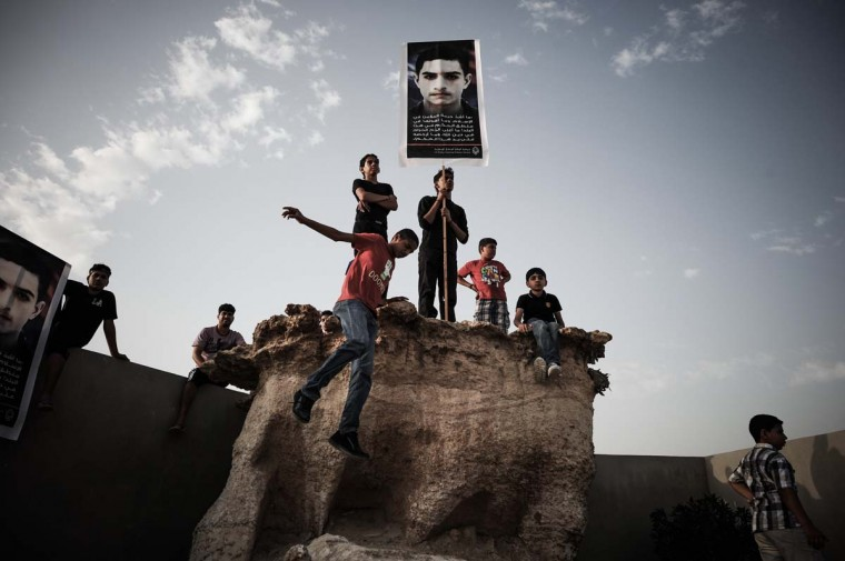 Bahraini youths hold a placard during the funeral of Mahmud al-Jaziri (portrait) on March 5, 2013 in Al Nabih Saleh Island, south of Manama. Al-Jaziri, 20, succumbed to his wounds on February 21 after he was shot during clashes between police and protesters marking the second anniversary of the February 14, 2011 uprising. (Mohammed Al-Shaikh/AFP/Getty Images)