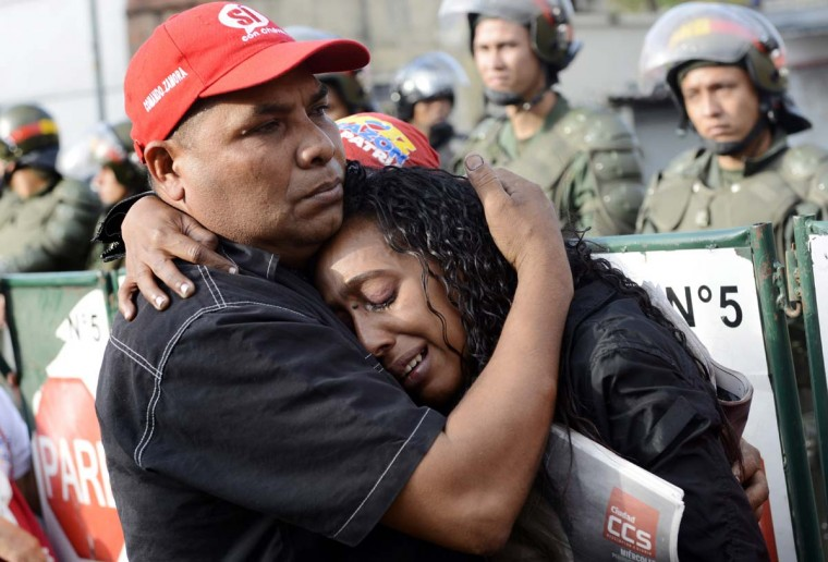 Supporters of the late Venezuelan President Hugo Chavez cry in front of the Military Hospital where he died on the eve, on March 6, 2013, in Caracas. Venezuela was plunged into uncertainty Wednesday after the death of President Hugo Chavez, who dominated the oil-rich country for 14 years and came to embody a resurgent Latin American left. (Leo Ramirez/AFP/Getty Images)
