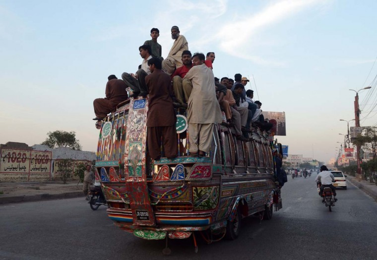 Pakistani passengers travel on a over loaded mini bus in Karachi on March 6, 2013. Karachi went on an indefinite strike, with businesses, shops, schools and transporters ordered to shutdown until police arrest those responsible for the city's worst bomb attack in years. The Muttahida Qaumi Movement (MQM), which controls most of Pakistan's largest city, ordered the strike three days after a powerful car bomb killed 50 people and wounded around 140 others in Shiite Muslim neighborhood Abbas Town. (Asif Hassan/AFP/Getty Images)