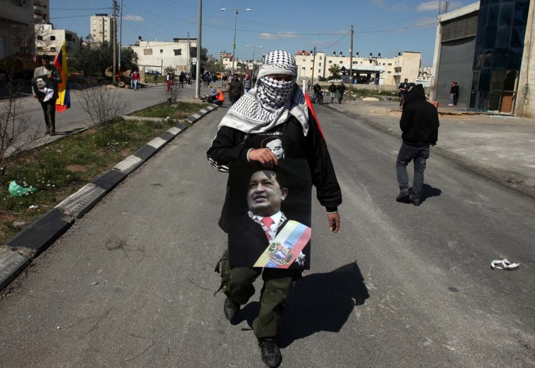 A Palestinian protestor, holding a picture of Venezuelan president Hugo Chavez in honor of his death, is seen during clashes with Israeli soldiers outside Ofer prison, near Ramallah, following a demonstration in support of Palestinian prisoners on hunger strike in Israeli jails on March 6, 2013. (Abbas Momani/AFP/Getty Images)