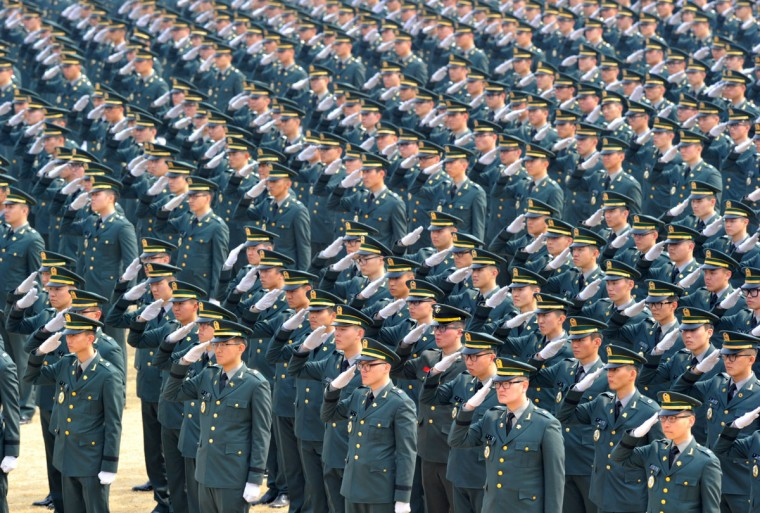 South Korean officers salute during the joint commission ceremony of 5,780 new officers of the army, navy, air force and marines at the Gyeryong military headquarters in Gyeryong on March 8, 2013, south of Seoul. An enraged North Korea responded to new UN sanctions with fresh threats of nuclear war on March 8, vowing to scrap peace pacts with South Korea as it upped the ante yet again after its recent atomic test. (Kim Jae-Hwan/AFP/Getty Images)