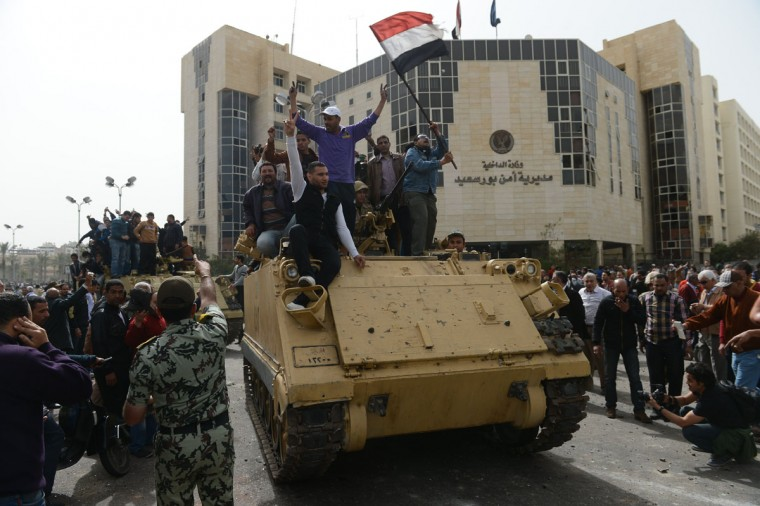 Egyptian protesters hold their national flag as they celebrate on an army tank outside Port Said's security headquarters on March 8, 2013, following the withdrawal of police forces from their headquarters in the Suez Canal city that has been the target of protesters and transferred its protection to the military, the interior ministry said. (Khaled Desouki/AFP/Getty Images)