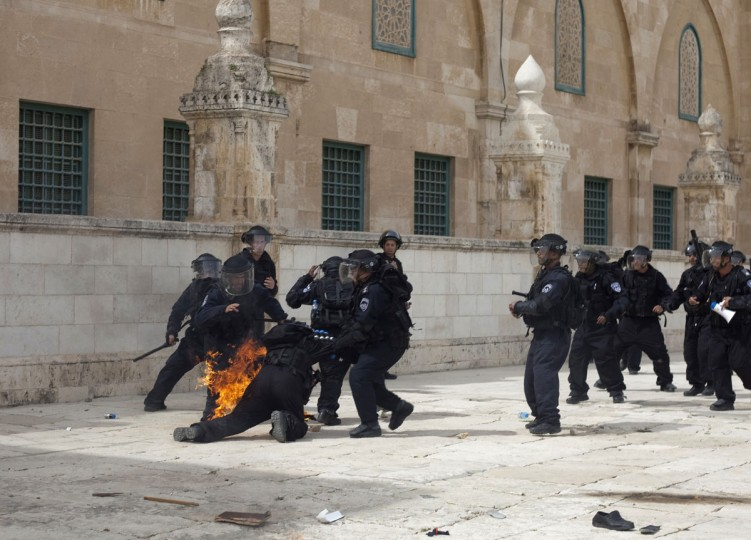 Israeli riot policemen help a comrade after a fire bomb was thrown at him during clashes with Palestinian demonstrators at Jerusalem's al-Aqsa mosque compound following Friday prayers on March 8, 2013. Palestinians enraged by reports that an Israeli policeman mishandled a Koran battled riot officers at Jerusalem's Al-Aqsa mosque compound with stones and petrol bombs, police and witnesses said. (STR/AFP/Getty Images)