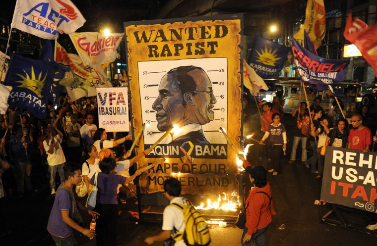 Protesters burn a poster bearing a joint caricature of U.S. President Barack Obama (L) and Philippine President Benigno Aquino as they march towards the Presidential Malacanang Palace to mark International Women's Day in Manila on March 8, 2013. The women's group called for gender equality, denounced the presence of the US military in the country, and blamed the Aquino government for surrendering to US policy. (Jay Directo/AFP/Getty Images)