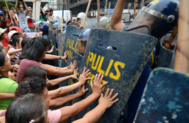 Protesters clash with anti-riot policemen as members of Philippine's group Gabriela attempt to march to the US embassy for a rally in Manila on March 8, 2013. The protest march by the Philippine's women group Gabriela was held as part of International Women's Day. (Ted Aljibe/AFP/Getty Images)