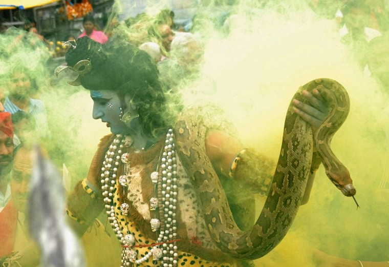 An Indian Hindu man dressed as Lord Shiva hold an 'ajgar' - snake - as he takes part in a religious procession on the eve of the Maha Shivratri festival in Jalandhar on March 9, 2013. Hindus mark the Maha Shivratri festival by offering special prayers and fasting to worship Lord Shiva, the lord of destruction. (Shammi Mehra/AFP/Getty Images)