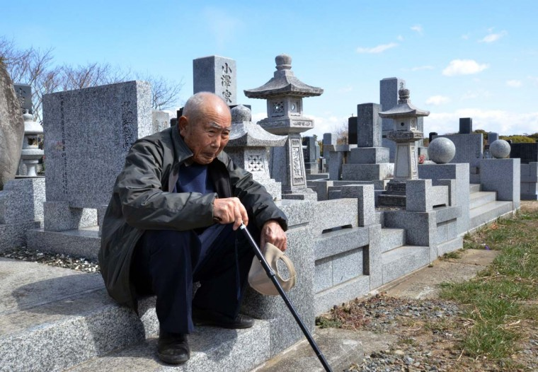 An elderly man sits as he and with his wife (not pictured) visit a cemetery to pay respects to their son who was killed in the March 2011 tsunami, in Minamisoma in Fukushima prefecture on March 11, 2013. March 11, 2013 marks the second anniversary of the 9.0 magnitude earthquake that sent a huge wall of water into the coast of the Tohoku region, splintering whole communities, ruining swathes of prime farmland and killing nearly 19,000 people. (Yoshikazu Tsuno/AFP/Getty Images)