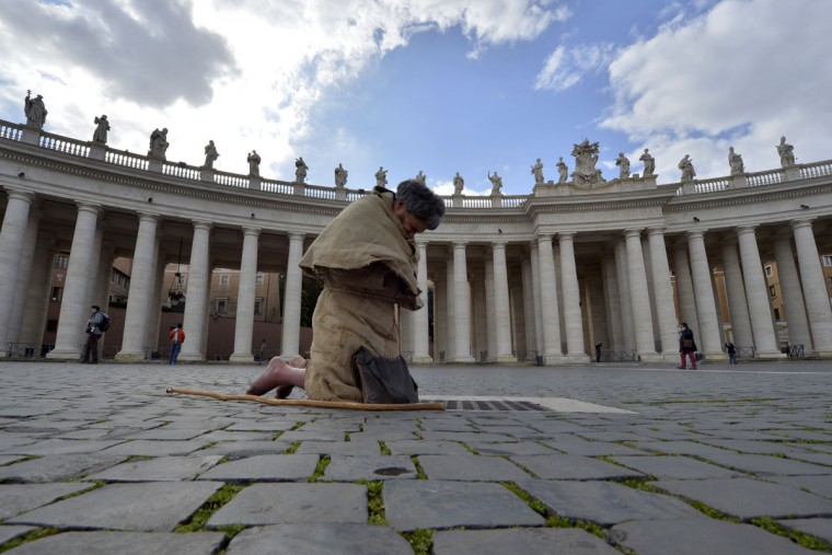 A barefoot faithful prays on St. Peter's square ahead of a conclave on March 12, 2013 at St. Peter's square at the Vatican. Cardinals moved into the Vatican on Tuesday as the suspense mounted ahead of a secret papal election with no clear frontrunner to steer the Catholic world through troubled waters. (Andreas Solaro/AFP/Getty Images)