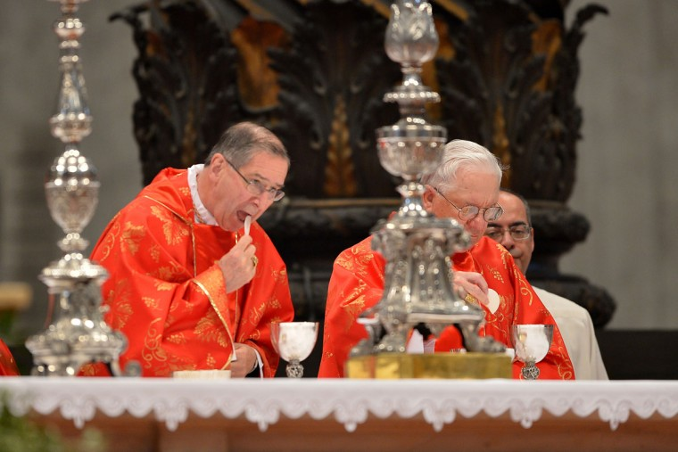 U.S. cardinal Roger Michael Mahony (L) takes the communion during a grand mass in St Peter's Basilica ahead of a papal election conclave on March 12, 2013 in St Peter's Basilica at the Vatican. (Gabriel Bouys/AFP/Getty Images)