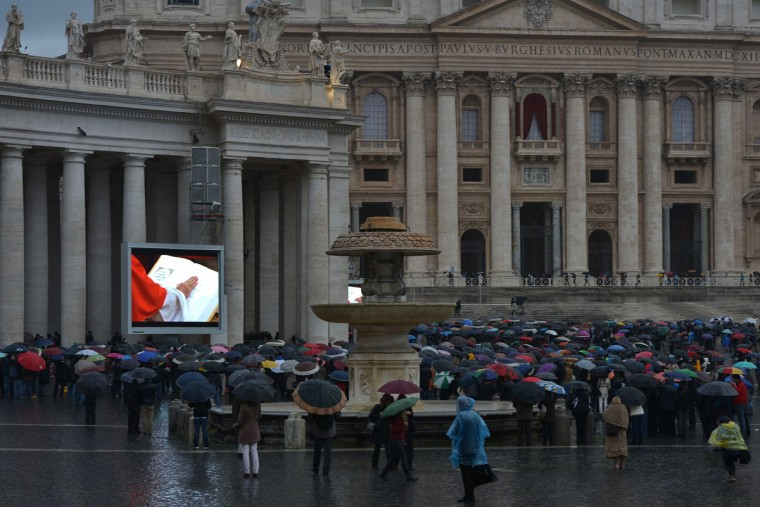 A crowd, holding umbrellas, looks at a giant screen showing the start of the papal election conclave, under a statue of St. Peter, at St Peter's square on March 12, 2013 at the Vatican. Cardinals prepared Tuesday for the start of an historic conclave to elect a new pope. (Gabriel Bouys/AFP/Getty Images)