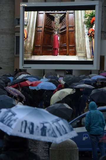 A crowd in St. Peter's Square, holding umbrellas, looks at a giant screen showing the start of the papal election conclave on March 12, 2013 at the Vatican. (Andreas Solaro/AFP/Getty Images)