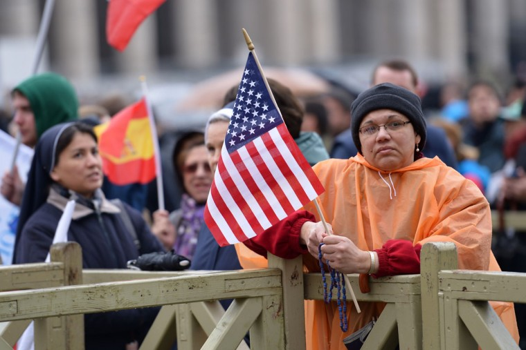 A faithful Catholic holds a U.S. flag at St. Peter's Square while waiting for the smoke announcing the result of the second vote of the papl conclave on March 13, 2013 at the Vatican. The 115 cardinals held a first inconclusive vote in the Sistine Chapel yesterday as they began the process of finding a successor to Benedict XVI. (Vincenzo Pinto/AFP/Getty Images)