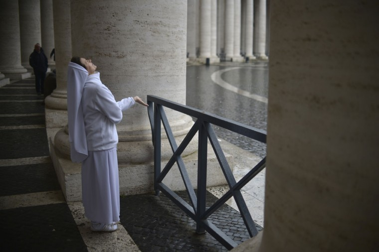 A nun waits under the colonnade as it is raining on St Peter's square on March 13, 2013 at the Vatican. Cardinals prepared for a second day of conclave behind the Vatican's walls to elect a pope today, with all eyes on a chimney that will signal when there is a new leader for the world's 1.2 billion Catholics. (Johannes Eisele/AFP/Getty Images)