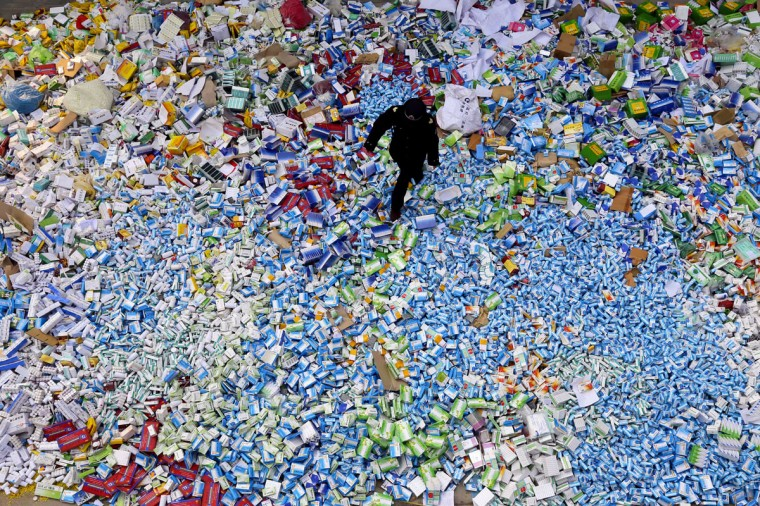 This picture taken on March 14 shows a Chinese policeman walking across a pile of fake medicines seized in Beijing in recent months, which were later destroyed. The rapid growth of Internet commerce has led to an explosion of counterfeit drugs sold around the world, with China the biggest source of fake medicines, pharmaceutical experts said as the illicit trade is now believed to be worth around 75 billion USD globally, with criminal gangs increasingly using the web to move their products across borders. (PHOTOSTR/AFP/Getty Images)