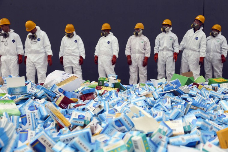 This picture taken on March 14 shows health workers preparing to destroy fake medicines seized in Beijing in recent months. (PHOTOSTR/AFP/Getty Images)