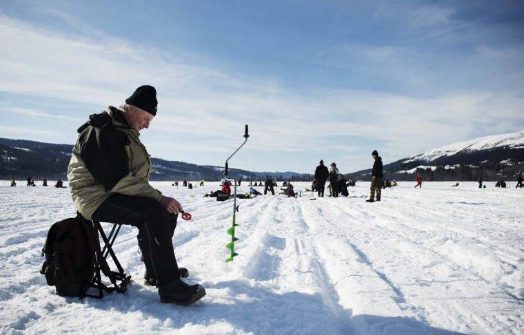 A man holds a fishing pole into a hole on the frozen Oster-Jansjon lake as he participates in an ice fishing contest in Are, Sweden on March 17, 2013. (Jonathan Nackstrand/AFP/Getty Images)