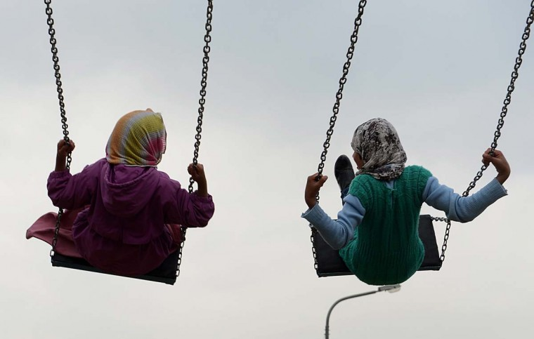 Young Afghan girls play on swings near The Kart-e-Sakhi shrine in Kabul on March 18, 2012. Despite massive injection of foreign aid since the fall of the Taliban in 2001, Afghanistan remains desperately poor with some of the lowest living standards in the world. (Shah Marai/AFP/Getty Images)