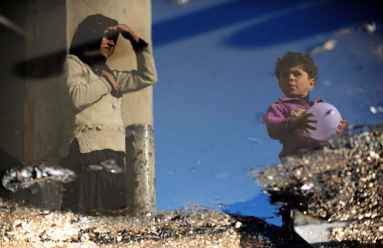 A Syrian internally displaced woman and child are reflected in a puddle of water in the Bab al-Hawa camp along the Turkish border in the northwestern Syrian province of Idlib, on March 18, 2013. The conflict in Syria between rebel forces and pro-government troops has killed at least 70,000 people, and forced more than one million Syrians to seek refuge abroad. (Bulent Kilic/AFP/Getty Images)