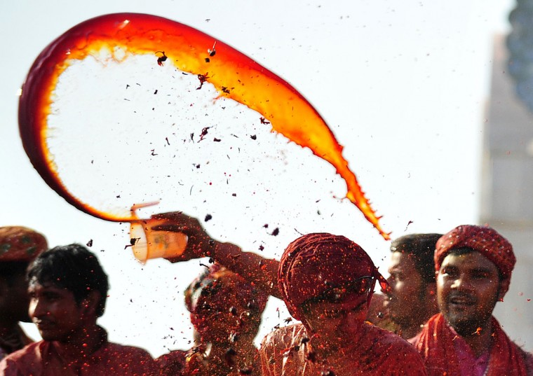 Hindus throw colored water at the Radha Rani temple during the Lathmar Holi festival in Barsana on March 21, 2013. Lathmar Holi is a local celebration, but it takes place well before the national Holi day on March 27. (Sanjay Kanojia/AFP/Getty Images)