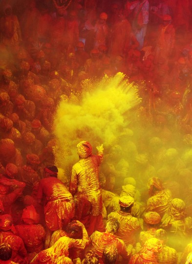Hindu worshippers throw colored powder at the Radha Rani temple during the Lathmar Holi festival in Barsana on March 21, 2013. Lathmar Holi is a local celebration, but it takes place well before the national Holi day on March 27.(Sanjay Kanojia/AFP/Getty Images)