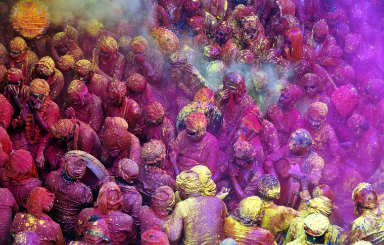 Hindu devotees throw colored powder at the Radha Rani temple during the Lathmar Holi festival in Barsana on March 21, 2013. Lathmar Holi is a local celebration, but it takes place well before the national Holi day on March 27. (Sanjay Kanojia/AFP/Getty Images)