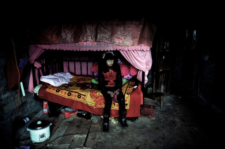 "Xiao Dan, a 12-year-old girl, sits on a bed in new clothes bought by her 28-year-old ""husband"" in a village in Liuzhi, southwest China's Guizhou province. The local government has investigated the issue and claimed the ""marriage"" was ""illegal,"" state media reported. The picture was taken on January 17, 2013. (STR/AFP/Getty Images)"