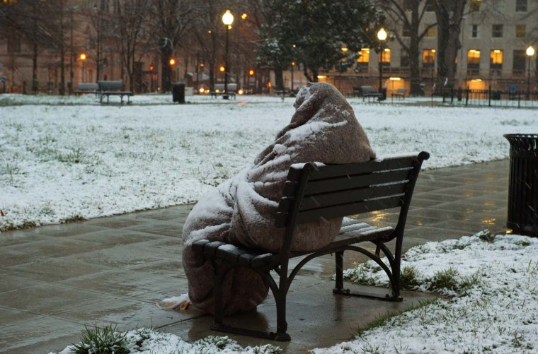 A homeless man sits covered in snow early on March 25, 2013 in Washington, DC. A messy Monday is in store for millions along the East Coast, with winter weather advisories warning of a mixture of snow and rain for Washington, DC, Philadelphia, metropolitan New York and parts of northeast New Jersey. (Karen Bleier/AFP/Getty Images)