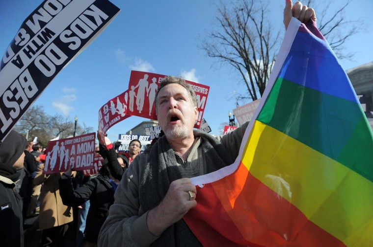 A same-sex marriage supporter (C) holds up a flag among anti-gay protesters in front of the U.S. Supreme Court on March 26, 2013 in Washington, DC. (Jewel Samad/AFP/Getty Images)