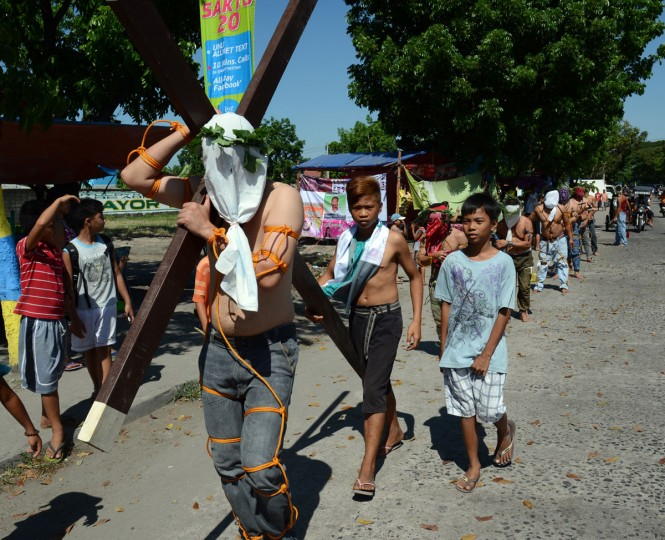 March 28, 2013: A penitent carries a cross while other flagellate themselves as they participate in symbolic ceremonies which commemorate Jesus Christ's crucifixion and resurrection on Holy Thursday in Angeles City, Pampanga province north of Manila. (Ted Aljibe/AFP/Getty Images)