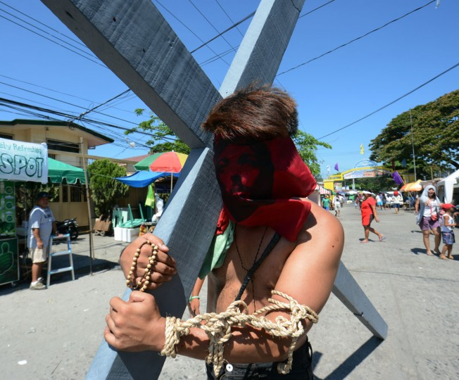 March 28, 2013: A penitent with his face covered with a portrait of Jesus carries a cross as he participates in symbolic ceremonies which commemorate Jesus Christ's crucifixion and resurrection on Holy Thursday in Angeles City, Pampanga province north of Manila. Crucifixions and self-flagellations are among the grisliest, but by no means the only extreme acts of penitence on show in the Philippines, one of Asia's largest Catholic outpost with about 75 million followers. (Ted Aljibe/AFP/Getty Images)