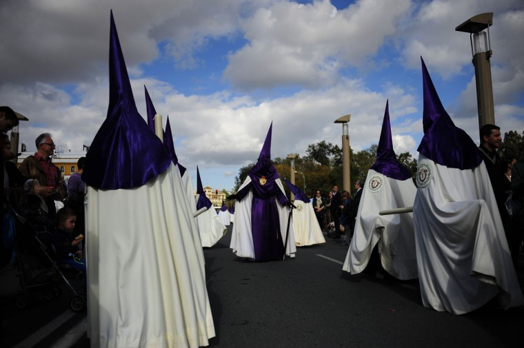 """March 28, 2013: Penitents of the """"Las Cigarreras"""" brotherhood cross a bridge in Sevilla during the Holy Week. (Cristina Quicler/AFP/Getty Images)"""