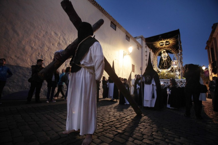 """March 28, 2013: The prisoner who will receive perdon today carries a cross as he takes part in a procession with penitents of the """"Nuestra Senora del Rosario"""" brotherhood during the Holy Week in La Laguna on the Spanish Canary island of Tenerife. (Desiree Martin/AFP/Getty Images"""